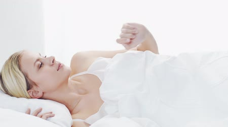 ébredés : Young woman lying in the bed. Beautiful blond sleeping girl. Morning in the bedroom. Health and rest concept.