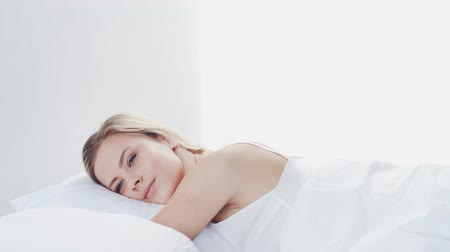 probudit se : Young woman lying in the bed with a smartphone. Beautiful blond awakening girl. Morning in the bedroom, daylight from the window.