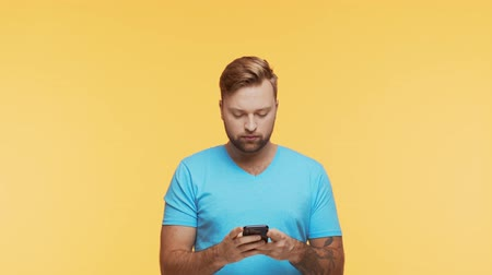 Expressive young man with a smartphone over vibrant background. Portrait of handsome person.
