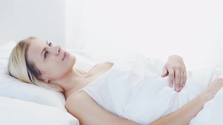 ленивый : Young woman lying in the bed. Beautiful blond sleeping girl. Morning in the bedroom. Health and rest concept.