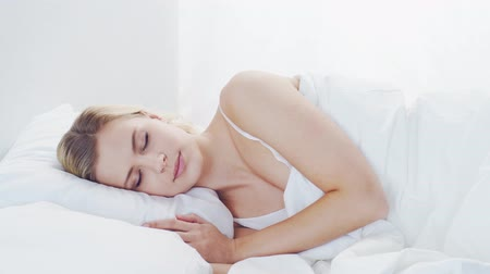 esneme : Young woman lying in the bed. Beautiful blond sleeping girl. Morning in the bedroom. Health and rest concept.