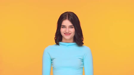 Studio portrait of young and expressive teenage girl over yellow background.