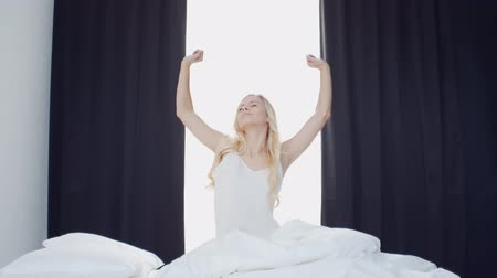 desperto : Young woman in the bed. Beautiful blond girl wakes up. Morning in the bedroom, daylight from the window. Health and rest.