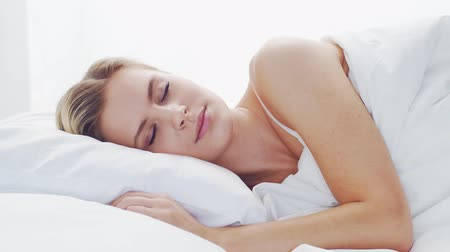 aufwachen : Young woman lying in the bed. Beautiful blond sleeping girl. Morning in the bedroom. Health and rest concept.