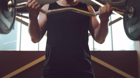 тренер : Athletic handsome male sportsman working in the gym using barbell. Strong and healthy bodybuilder abdominal training exercises. Sport, fitness, workout and lifestyle.