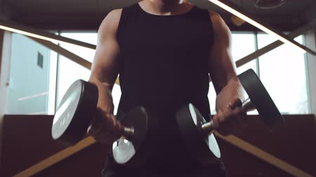 тренер : Athletic handsome male sportsman working in the gym using dumbbells. Strong and healthy bodybuilder abdominal training exercises. Sport, fitness, workout and lifestyle.