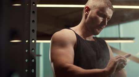 тренер : Athletic handsome male sportsman working in the gym using talcum powder. Strong and healthy bodybuilder abdominal training exercises. Sport, fitness, workout and lifestyle.