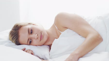 ébredés : Young woman lying in the bed with a smartphone. Beautiful blond awakening girl. Morning in the bedroom, daylight from the window.