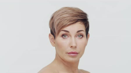 procedimento : Close-up of middle aged mature woman over white bacjground. Portrait of mature lady. Plastic surgery, beauty injections and cosmetology. Stock Footage