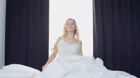 пробуждение : Young woman in the bed. Beautiful blond girl wakes up. Morning in the bedroom, daylight from the window. Health and rest.