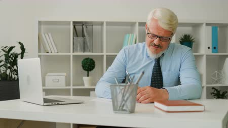 ağarmış : Adult caucasian man with glasses in blue shirt and tie sitting on the desk at office, writing something on a sheet of paper. Indoor.