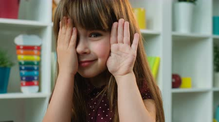 hides : Cute little girl closes and opens his hands over her face. Kids room background. Close up Stock Footage