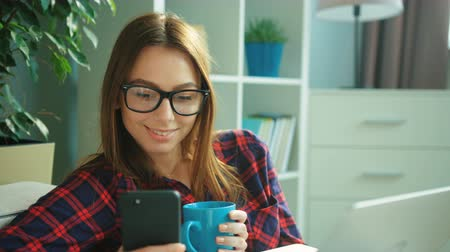szemüveg : Beautiful young woman wearing glasses using smartphone, drinking coffee and looking straight at the camera and smiling while sitting on the couch at home. Portrait shot. close up Stock mozgókép