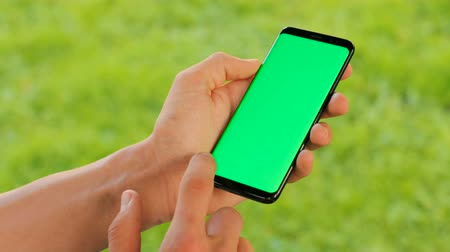 blank : Male hand holding black smartphone with green screen on green grass background. Outdoors in park. Man scrolling, tapping on touchscreen. Chroma key. Close up.