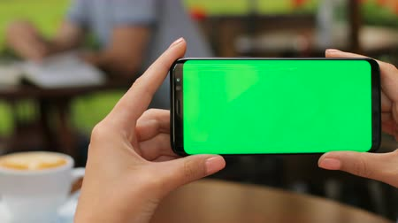érintőképernyő : Close up female hands holding black smartphone with green screen while sitting outdoors in the cafe. Horizontal. Woman drinking coffee. Chroma key Stock mozgókép