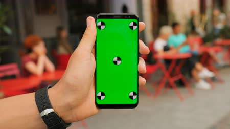 в чате : Man holding black smartphone with green screen on street cafe background. Close up. Chroma key. Tracking motion