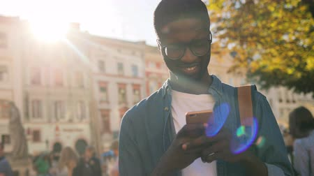 városi : Attractive young african american man with glasses in blue shirt using mobile phone for chatting with friend standing in city center.