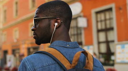 sluch : Back view of african american tourist listening to music using earphones and smart phone going in city. Outdoor.