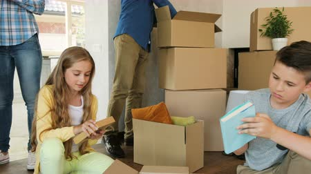 проведение : Beatiful caucasian family opening and pulling out things from the box and having fun. Стоковые видеозаписи