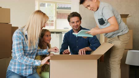 проведение : Beatiful happy family opening big cardboard box while they moving to the new house.