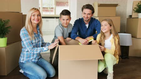 проведение : Portrait of happy family opening big cardboard box, turning to the camera and smiling. Close up shot.