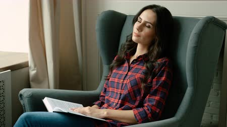 enciclopédia : Attractive young woman napping, sleeping on soft chair. Woman got nap while reading a book on chair living room. Close up Stock Footage