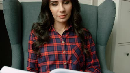 enciclopédia : Young attractive woman sitting in modern arm chair and reading interesting book. Close up