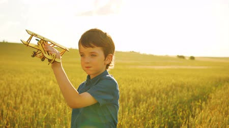 paper airplane : Young beatiful boy playing with wooden plane in the field at hte sunset background.