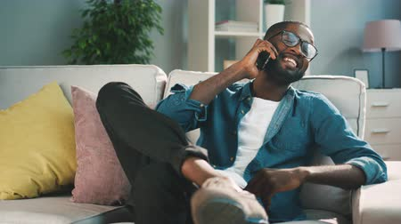 etnisite : Attractive african man celling on the phone while sitting on the sofa at living room. Young man using smart phone for chating. Stok Video