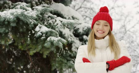 шляпа : Portrait shot of the pretty blonde woman in white coat and red hat standing in front of the camera with hands crossed and smiling close to the green tree with snow. Outdoors.