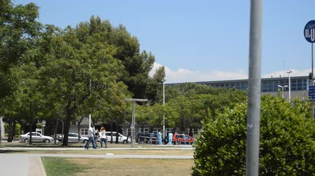estação de trabalho : This is footage of people standing, sitting on benches and walking in a park by the entrance of a huge hospital. Three tall black men walk beside nurses and doctors.