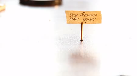 provérbio : Hand writing on the label Stop dreaming start doing.