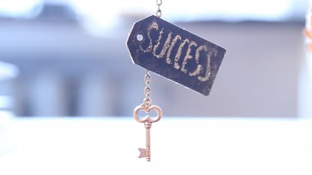 success : Golden key with word success on a chain, toned.