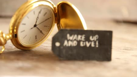 motivasyonel : wake up and live idea, inscription on the label and gold pocket watch