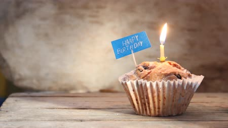 happy : Cupcake with a birthday candle and happy birthday label.