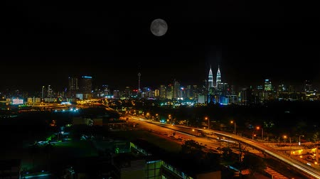 night scene : Kuala Lumpur city. Time lapse of moon falling on dark night sky