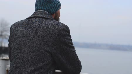anlamı : A man in a coat standing at the river jetty Stok Video