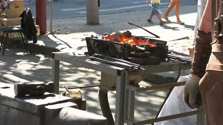 coppersmith : Smith takes the hammer from the anvil. Blacksmith forges metal on the street proud Stock Footage