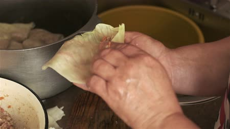 chop up : A woman prepares stuffed cabbage. A grown woman cook cabbage at home Stock Footage
