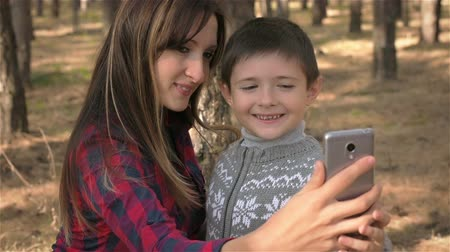 Картинки : Happy mother and son are photographed in woods. Close up. Mother and son are taking selfie on mobile phone in wood