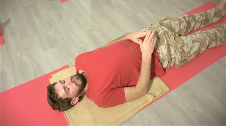 pozisyon : Guy resting on training in acrobatics. Many people are training for Acro-yoga. Fitness at the athletic club. Young people for healthy lifestyle Stok Video