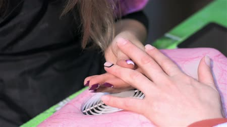 mimos : Staining nails with black lacquer. Close up. Actual process of performing manicure. Woman in nail salon