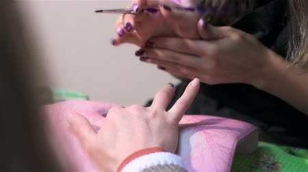 mimos : Dyeing nails red varnish. Actual process of performing manicure. Woman in nail salon Stock Footage