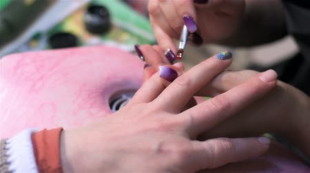 mimos : Dyeing nails red varnish. Close up. Actual process of performing manicure. Woman in nail salon Stock Footage