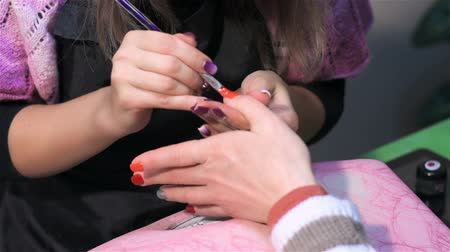 mimos : Painting nails in orange. Actual process of performing manicure. Woman in nail salon