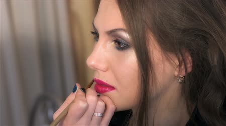 szminka : Makeup artist paints womans lips with red lipstick. Close up. Woman visits beauty salon. Creating individual hairstyles and makeup in beauty salon