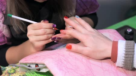 manicure : Painting nails in orange at nail salon. Actual process of performing manicure. Woman in nail salon Stock Footage