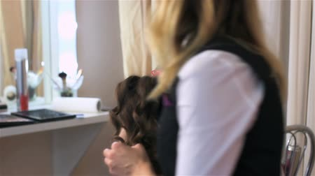 головной убор : Woman turns around on chair in hairdressing salon. Woman visits beauty salon. Creating individual hairstyles in beauty salon