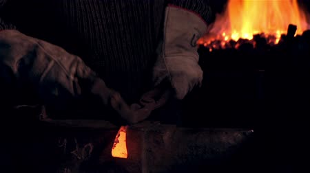 pour out : Blacksmith hammer hitting red-hot metal workpiece. Man working at the forge. Worker heavy metallurgy