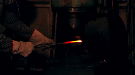 młyn : Large mechanical hammer hits hot metal Man working at the forge. Worker heavy metallurgy